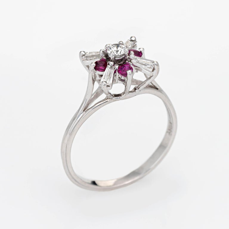 Stylish vintage diamond & ruby cocktail ring crafted in 18 karat white gold.   Tapered baguette cut diamonds and one round brilliant cut diamond total an estimated 0.66 carats (estimated at G-H color and VS2-SI1 clarity). Four estimated 0.03 carat