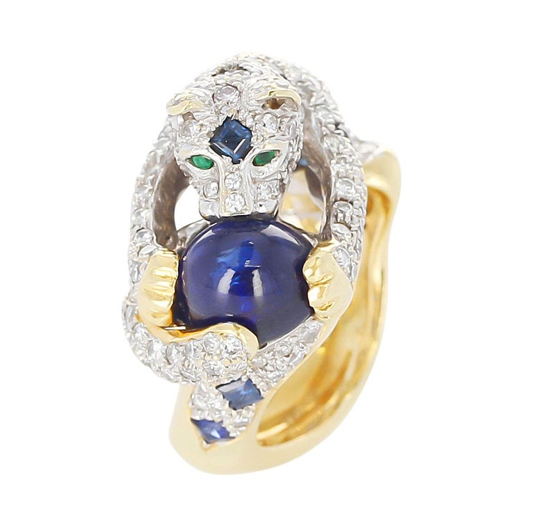A Diamond, Sapphire, and Emerald Panther Ring in 18 Karat Gold. The Panther is holding a sapphire, and the eyes are Emerald. The sapphire weighs 6.45 carats, and the diamodns weigh 3.60 carats. The total weight is 22.09 grams. Ring Size US 6.25.
