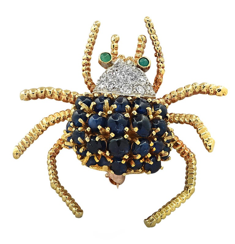 Enchanting spider brooch pin crafted in 18 karat yellow and white gold, adorned with 25 blue oval sapphire cabochons weighing approximately 2.50 carats total, 16 single cut diamonds weighing approximately .20 carats total, G color, VS clarity and 2