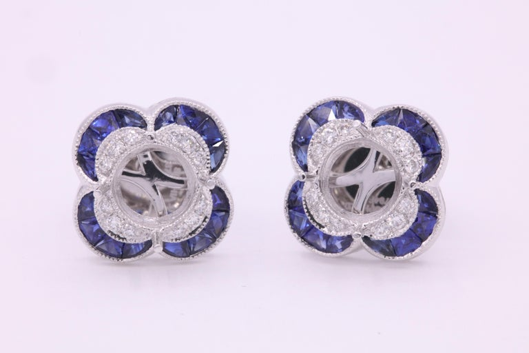 Gorgeous Art Deco style bezel earrings featuring vibrant blue sapphires weighing 1.05 carats and round brilliants weighing 0.14 carats crafted in platinum. Measures 3/8-1/4