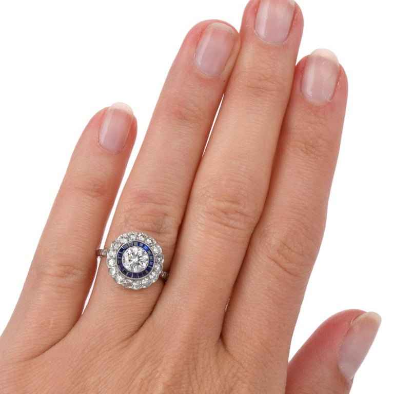 This right hand engagement or  Cocktail Ring was inspired in a Double Halo  and crafted in Platinum. A bright white round brilliant cut Diamond is bezel set in the center with a rings of bezel set Sapphire and prong set round Diamonds surround.