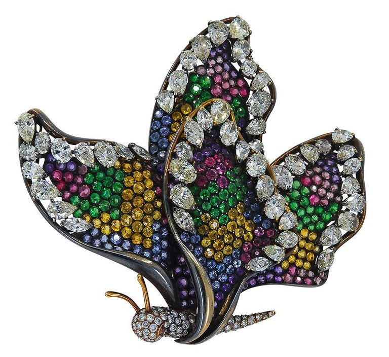 Diamond Sapphire Multicolor Pave Butterfly Brooch in 18k gold with black rhodium.  Blue, yellow, green, pink sapphire pavé – with white diamonds in oval, pear, marquise and round shapes.  Measures approx. 3 1/4″ in length, 3″ in width. French Assay