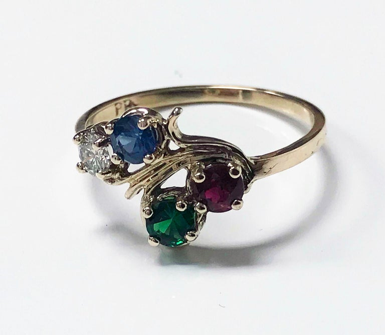 Diamond, Sapphire, Ruby and Tsavorite Ring. Diamond 0.15 ct, VS clarity, H colour, Sapphire medium light moderately strong blue, 0.20ct, Ruby, medium moderately strong Red, 0.,18 ct, fine green tsavorite, 0.17 ct The mount of twist twig design,