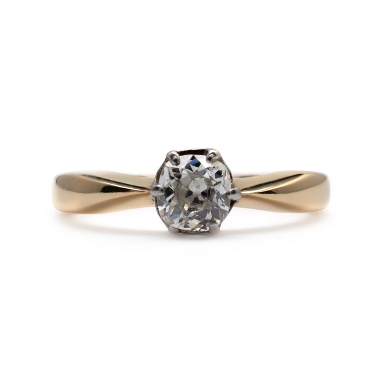 This diamond solitaire engagement ring is set with a cushion-cut 0.50-carat diamond.  Crafted in 18ct yellow gold, the shank has beveled edges with pinched reverse tapered shoulders. The diamond is neatly secured into a decorative rex style