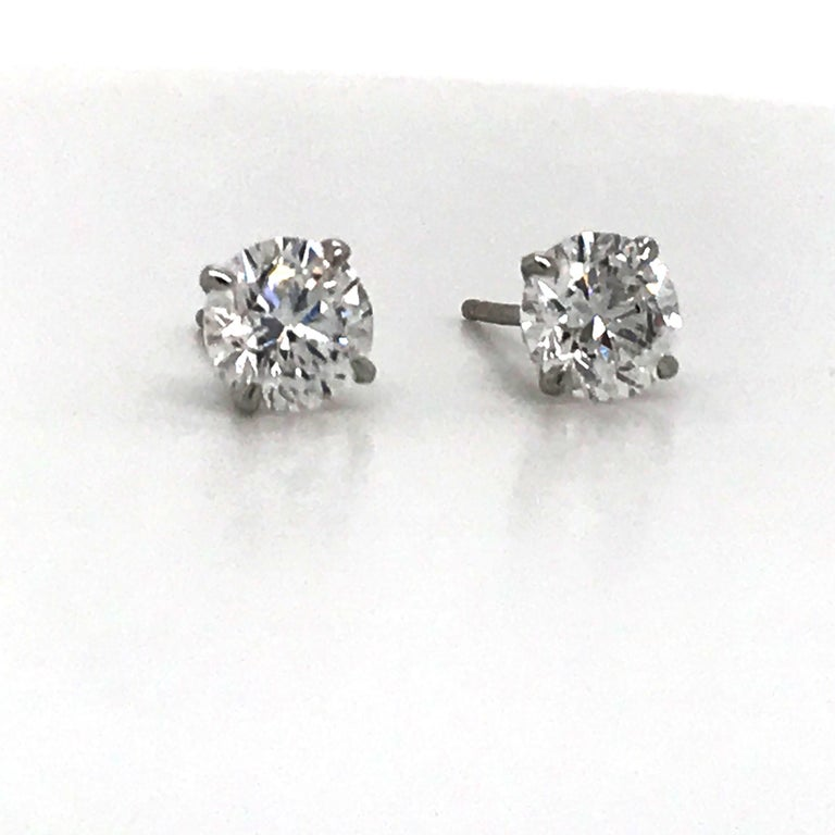 Diamond stud earrings weighing 1.40 carats in a 14k white gold 4 prong martini setting. Color E-F Clartiy SI2