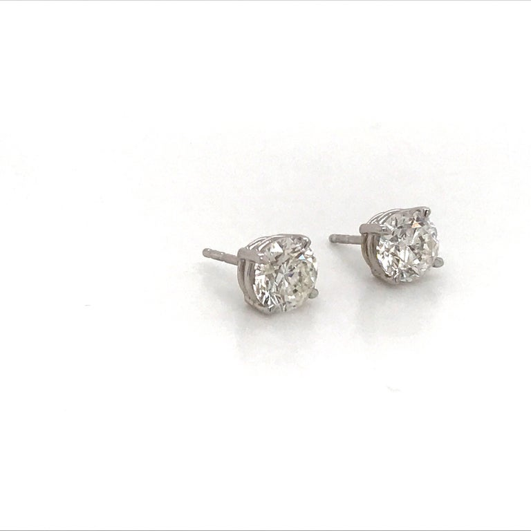 14K White gold diamond stud earrings weighing 1.80 carats in a 4 prong classic setting. Settings can be switched to martini or champagne.  Color I-J Clarity SI1  Brilliant pair of studs.