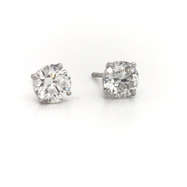 Diamond stud earrings weighing 1.96 carats in a 4 prong champagne setting, 18k white gold. Color H-I Clarity I1