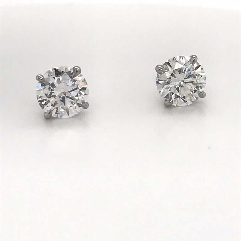 14K White gold diamond stud earrings weighing 2.03 carats in a 4 prong martini setting. Color F-G Clarity SI3-I1