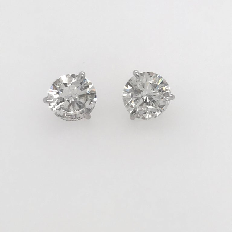 A pair of diamond stud earrings weighing 3.06 carats in a 18k white gold 3 prong champagne setting. Color H Clarity SI3-I1