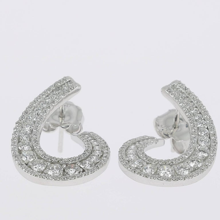 The Swirl Earrings are set with 3 Rows of White Diamonds. The Diamond weight is 1.97 Carats. All Diamonds are GVS qualities. The earrings have Clip Closing security. The Earrings are 18K White Gold. Also available in 18 Karat Rose Gold and 18K
