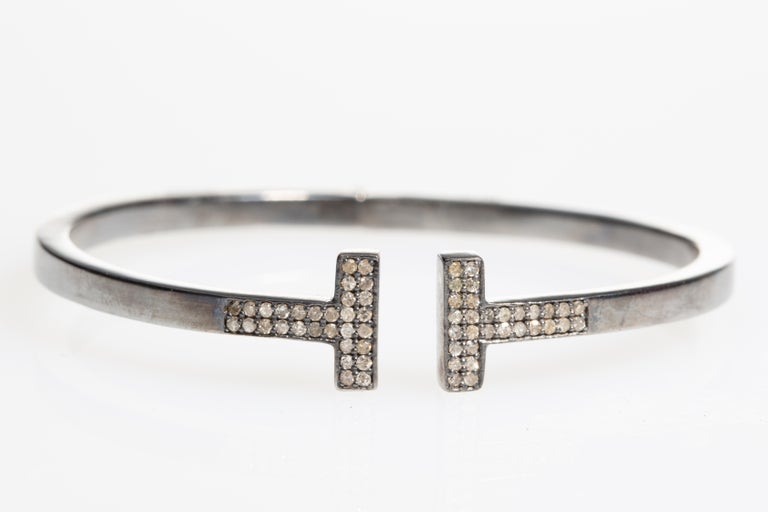A diamond T Bracelet in an oxidized sterling silver. Spring hinge at the back for easy on and off. Oval shape keeps the diamond display on top of the wrist. A take on Tiffany, but not. Diamond weight is .55 carats.