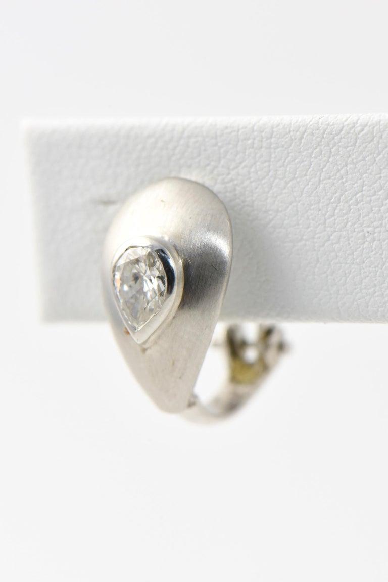 Brushed 14K white gold teardrop earrings with a bezel-set 0.35 carat pear-cut diamond in the center of each. Clip backs. Diamonds: G-H VS2-SI1. Some wear.