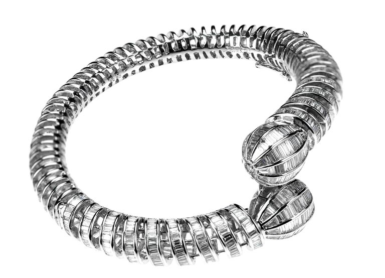 A dazzling diamond bangle set with baguette-cut diamonds and round brilliant cut diamonds. The twisted spring design gradually opening into two connected diamond-set knops, set with graduating baguette-cut diamonds to circular-cut diamond points.