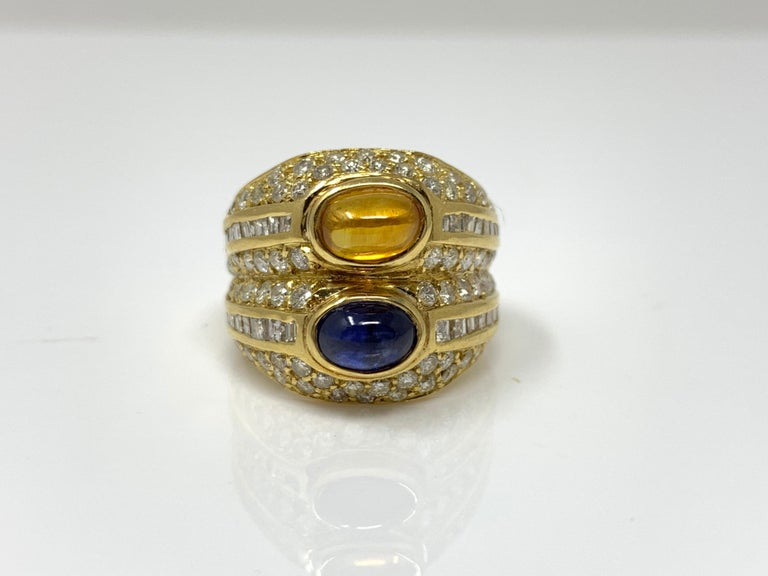 This bold and beautiful ring was wonderfully designed and masterfully handcrafted in 18k yellow gold. The ring is set with two cabochons blue sapphire and yellow sapphire weighing 2 carat , small white diamonds weighing 2.20 carat with SI clarity