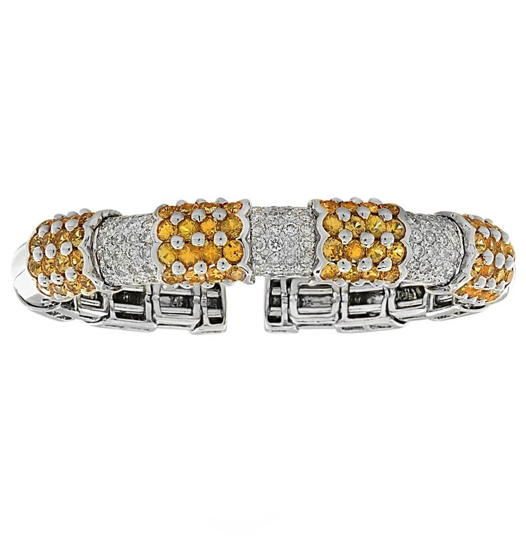 Stunning bangle bracelet crafted in 18 Karat white and yellow gold featuring 72 round brilliant cut diamonds weighing approximately 2 carats total, G color, VS clarity and 32 Yellow Sapphires weighing approximately 2 carats total. The diamonds are