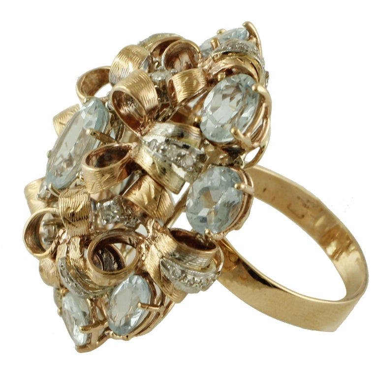 Marvelous cocktail ring in 9k white and yellow gold structure. The ring features a curly yellow gold structure, where diamonds and aquamarines are setted.  This particular ring is totally handmade by Italian master goldsmiths Diamonds 0.58