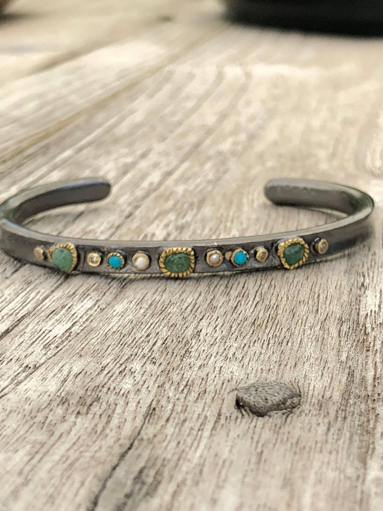 The bangle bracelet EKO is hand made and designed in Paris. Made in 14K gold and oxidized sterling silver, the bracelet is enhanced by tiny diamonds (0,08 ct.), emerald (0,49 ct.), turquoises and pearls.  Perfect stacking with our HUMA and BIBO