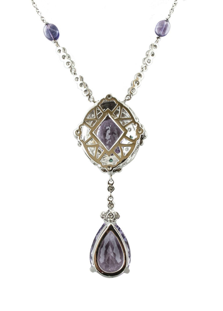 Very elegant pendant necklace in 14k white gold mounted on the pendant with one drop shape amethyst and one oval shape amethyst surrounded by 0.32 ct of little emeralds and 1.92 ct of little diamonds. The row is in 14K white gold and embellished