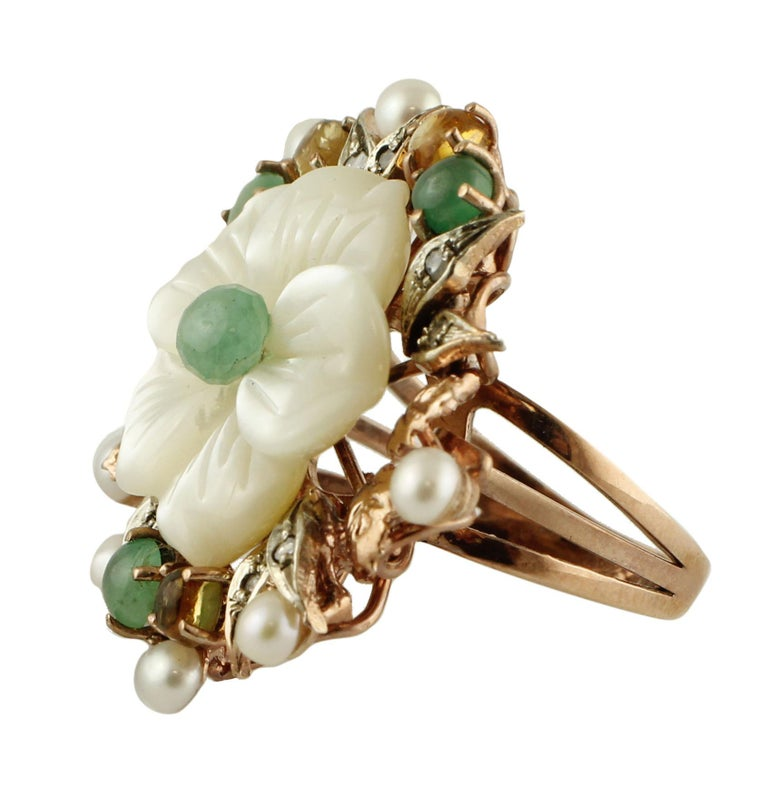 Amazing ring in 9 kt rose gold and silver, (diameter 2.8 cm), enriched with 0.13 ct of diamonds, 2.08 ct of emeralds and yellow sapphires, 1.90 g of mother-of-pearl flower in the center, 1.30 g of little around it that decorate this fascinating