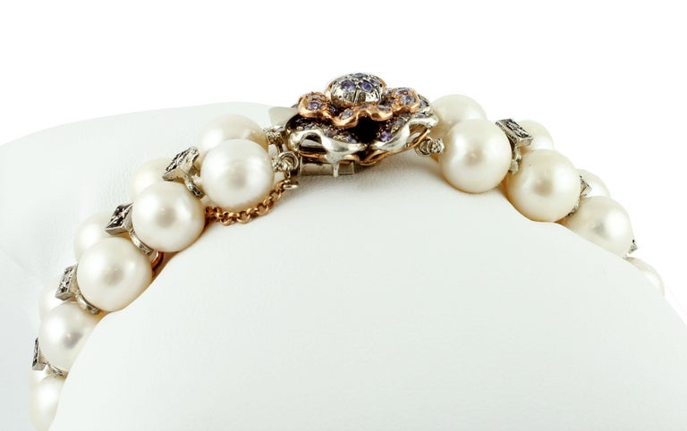 Beautiful beaded bracelet in 9k rose gold and silver structure, realized with two rows of south sea pearls enriched by decorations in silver and diamonds, and a flower-shaped closure in gold and silver structure studded with hard stone.  The origin