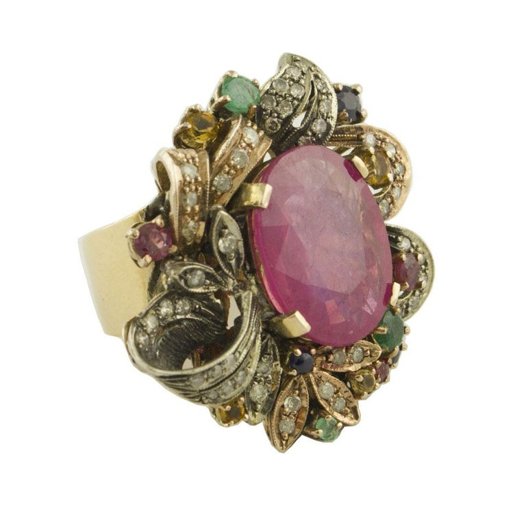 Unique ring in 9K rose gold and silver composed of an amazing ruby in the center surrounded by diamonds, rubies, emeralds, blue sapphire and yellow sapphires Diamonds 0.77 ct  Rubies, Emeralds, Sapphires 13.92 ct  Total Weight 16.80 g R.F +