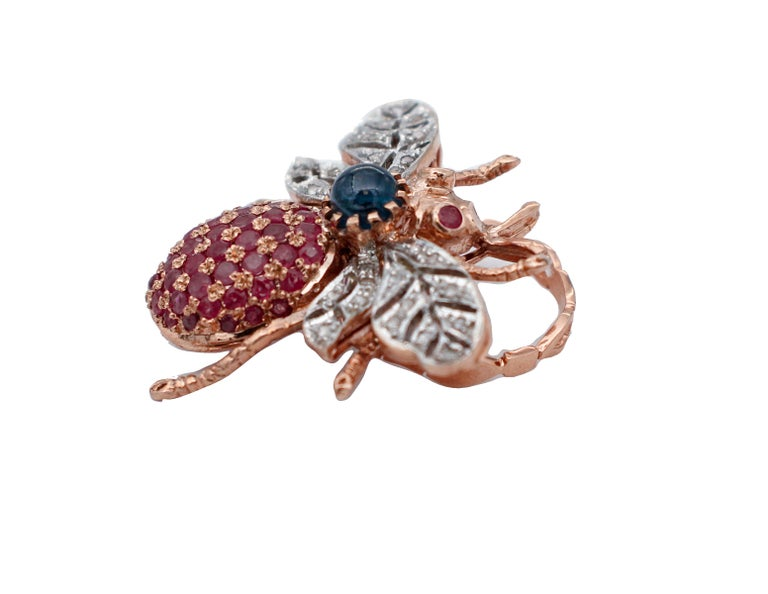 Particular fashion ring in 9 kt rose gold and silver structure with the shape of a fly. It has two rubies as eyes and one blue sapphire on the neck. The body is studded with rubies and its wings with little diamonds. The origin of this ring goes