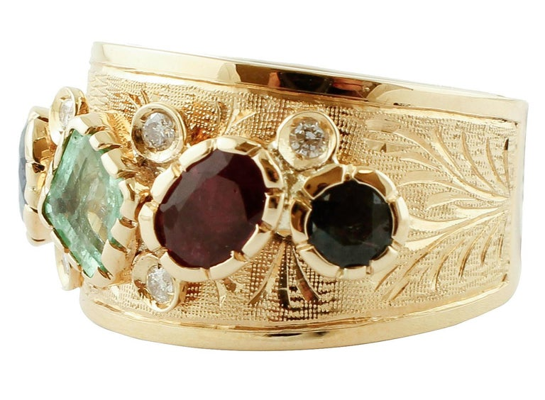 Band ring in 14k yellow gold with beautiful decorations of emeralds, rubies, blue sapphires and diamonds. The origin of this ring dates probably back to the 1980s, it was totally handmade by Italian master goldsmiths and it is in perfect