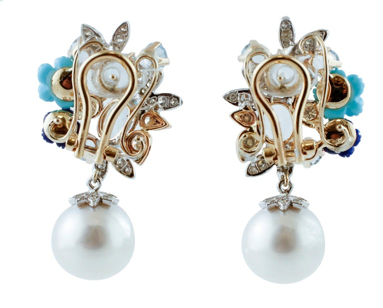 Elegant and refine pair of clip-on/drop earrings realized with flower design in 14K rose and white gold structure and mounted with 1.26 ct of diamonds, 5.50 ct of oval and round shape aquamarines, 4.94 g of 2 glossy pearls and 4 very little pearls,