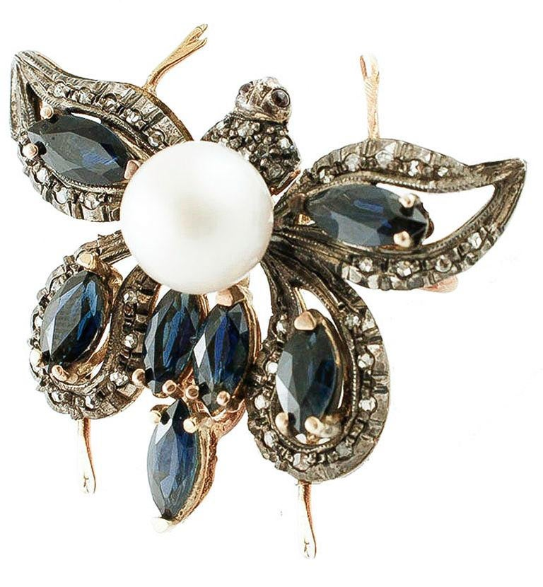 Unique design butterfly shape pendant necklace and brooch at the same time, mounted with 1.50 g of glossy pearl in the center of the body, 4.73 ct of 7 marquise cut blue sapphires on the boby and on the wings and it's studded all around by 0.30 ct