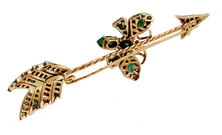 Particular vintage brooch in 9 kt rose gold and silver structure, featuring an arrow where a lovely butterfly is set. The arrow and the butterfly are studded by diamonds, rubies, emeralds and blue sapphires. This brooch is totally handmade by
