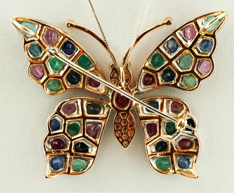 Vintage brooch/pendant in 9k rose gold and silver structure with butterfly design. The butterfly's body is realized in 9k rose gold with diamonds and a central ruby. The butterfly's wings are studded with diamonds, emeralds, rubies and blue