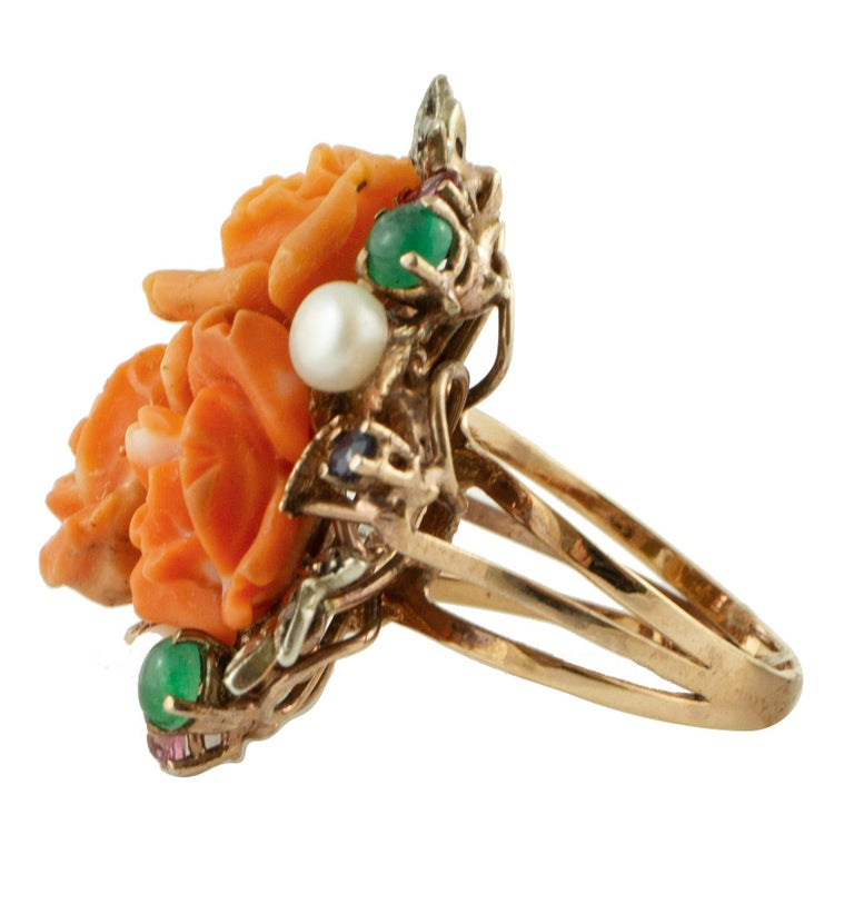 Amazing retrò cluster ring in 9K rose gold and silver mounted with 3.7 g of coral flowers in the center, surrounded by leaves detailes studded with 0.12 ct of diamonds and adorned around with 1.21 little blue and yellow sapphires, rubies, emeralds,