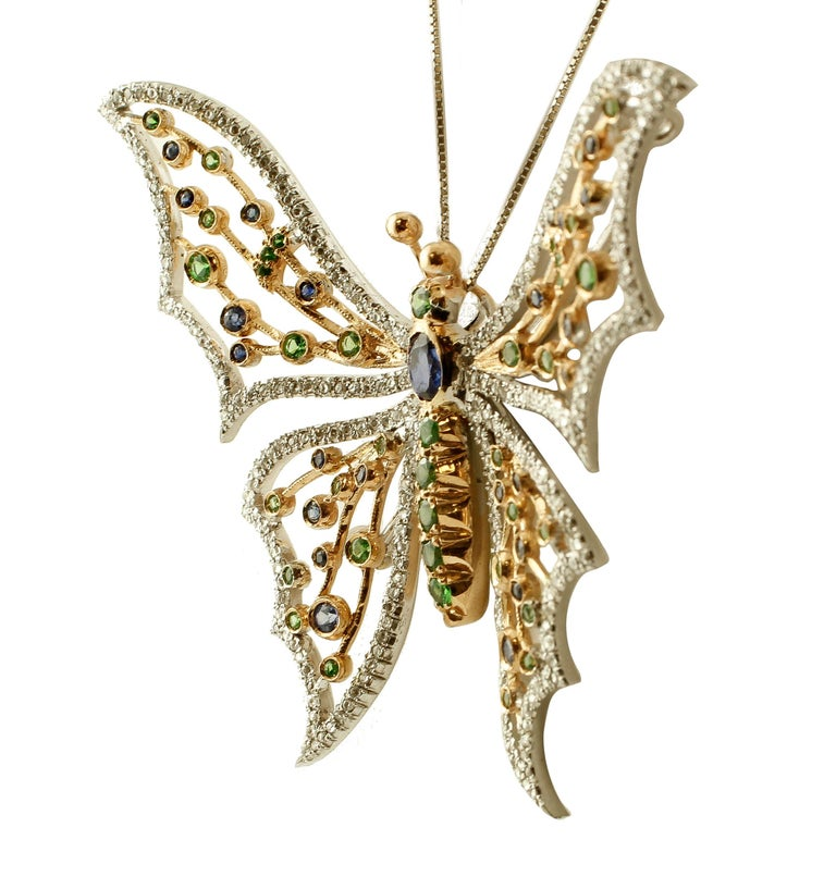 Beautiful vintage butterfly brooch/pendant in 14 kt white and yellow gold totally studded with diamonds, blue sapphires and tsavorite (chain not included). This brooch/pendant is totally handmade by Italian master goldsmiths. Diamonds 1.23 ct,