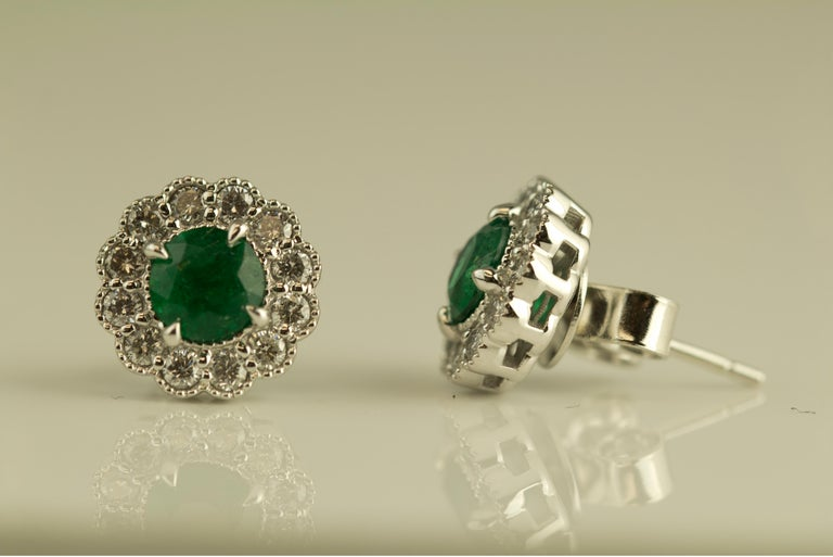 These beautiful earrings have two round cut emerald centers, surrounded by a halo of round white diamonds. Delicate milgrain work throughout further enhances the appeal of the piece.  Total emerald weight 0.95 carats Total diamond weight 0.52
