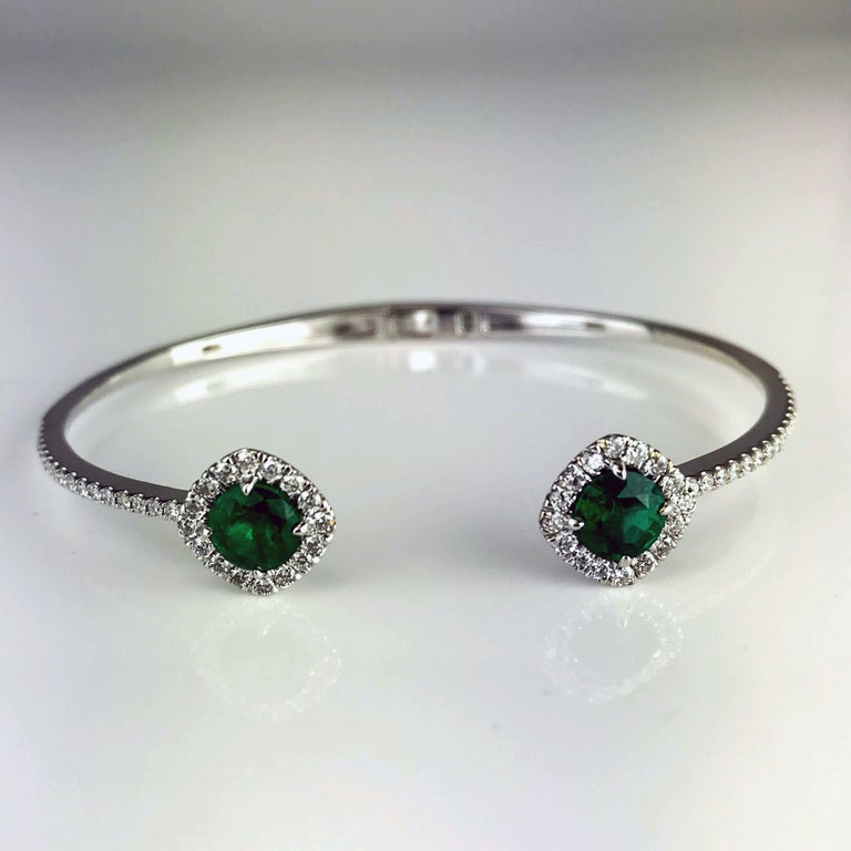 The heads on this bangle are two round cut emeralds, surrounded by a tight halo of round white diamonds, which also extends to the halfway point of the bangle. The halo is set in a way to give the overall impression of a cushion cut stone.  Total