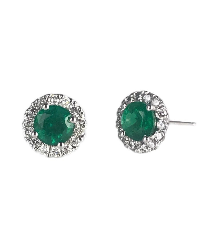 These earrings feature 1.3 carats round emeralds in Diamond halo. The bright vibrant green of these earrings will be a gorgeous accompaniment to your look.  The emerald centers are 5.5mm rounds, totaling 1.30 carats. Diamonds total 0.42 carats.  Set