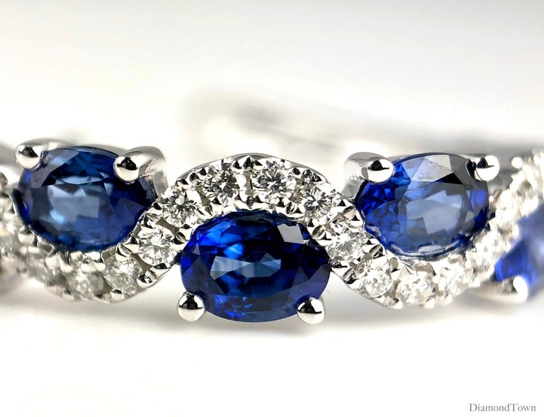 (DiamondTown) These lovely earrings each feature five oval cut vivid blue sapphires (total weight 2.13 carats) inside a weaving curve of round white diamonds (diamond weight 0.32 carats).  The earrings close by lever-back and are set in 18k White
