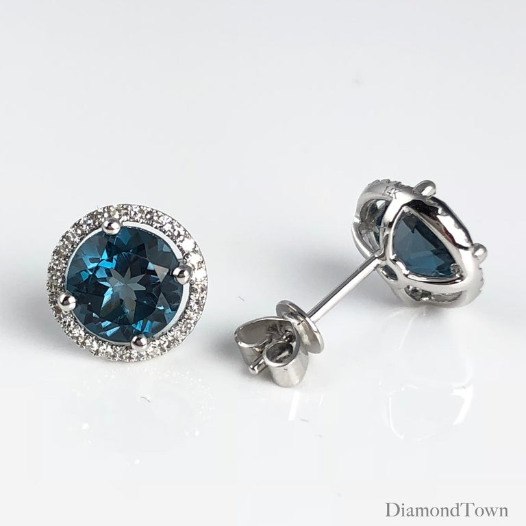 These stunning halo stud earrings feature 3.58 carats London Blue Topaz, surrounded by a halo of round white diamonds.  Center: two round London Blue Topaz stones total 3.58 carats Diamond Halo: 56 round diamonds total 0.16 carats Set in 14k White