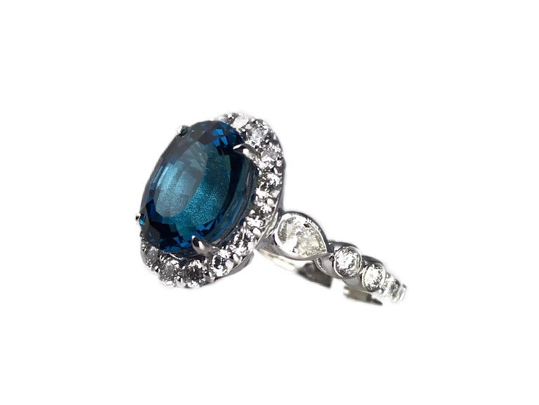 This gorgeous ring holds a 11mm x 9mm oval cut London Blue Topaz center, surrounded in a halo of round diamonds, with additional round and pear shape diamonds down the shank. Set in 14k White Gold.  Total blue topaz weight - 5.35 carats Total white