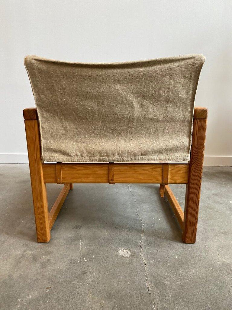 """Karin Mobring's """"Diana"""" Sling chair manufactured by Ikea in 1972 in Sweden. It is made of dark stained pine and covered with a cotton canvas fabric attached by three leather straps."""