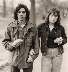 A young man and his girlfriend with hot dogs in the park