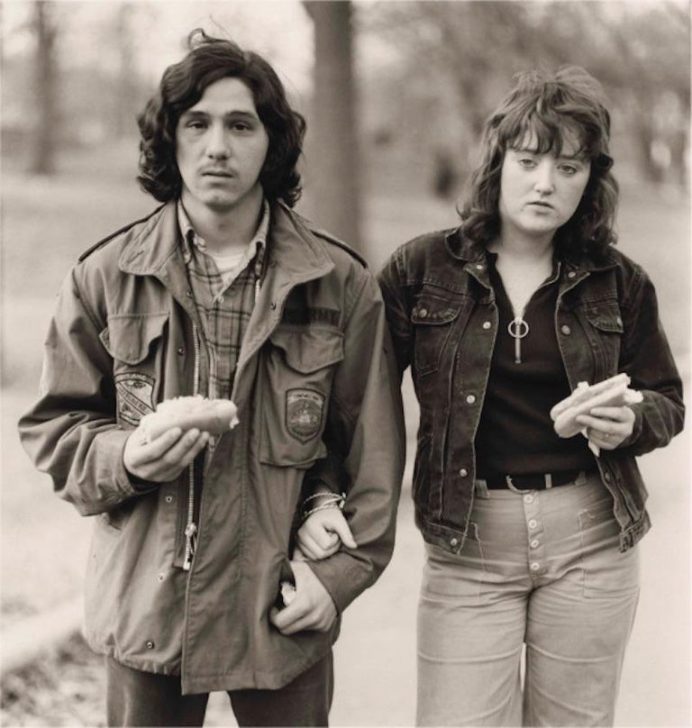 Diane Arbus Portrait Photograph - A young man and his girlfriend with hot dogs in the park