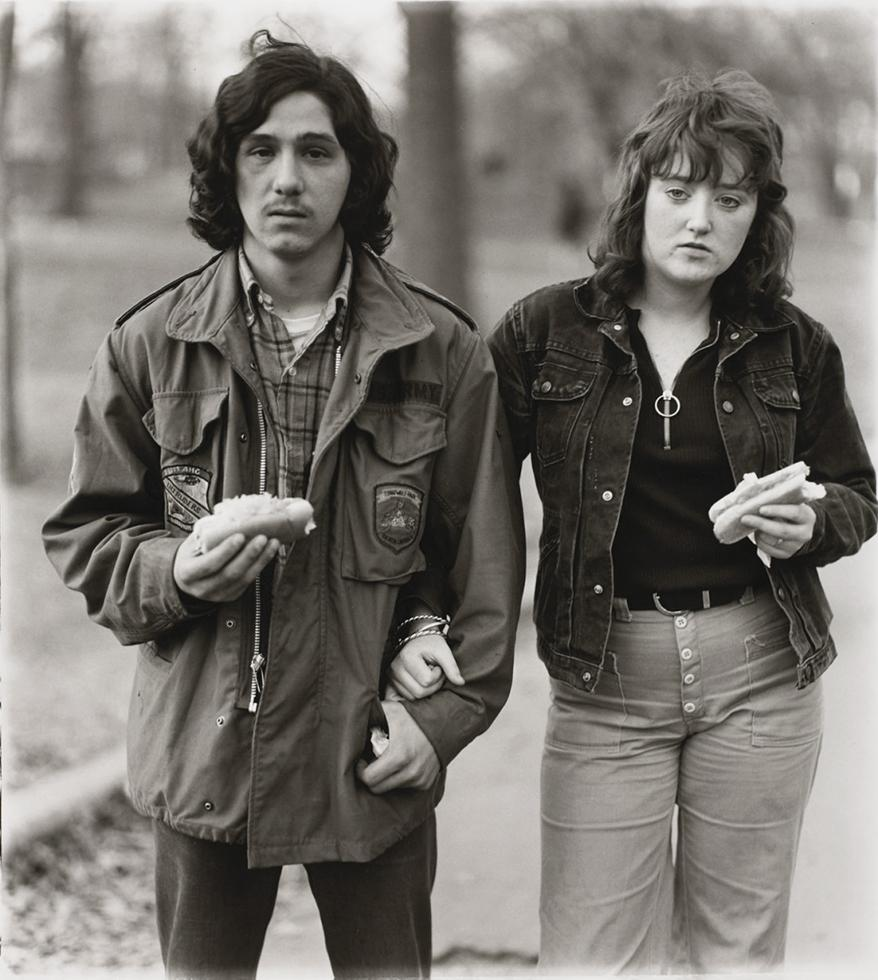 A young man and his girlfriend with hot dogs in the park, N.Y.C. 1971