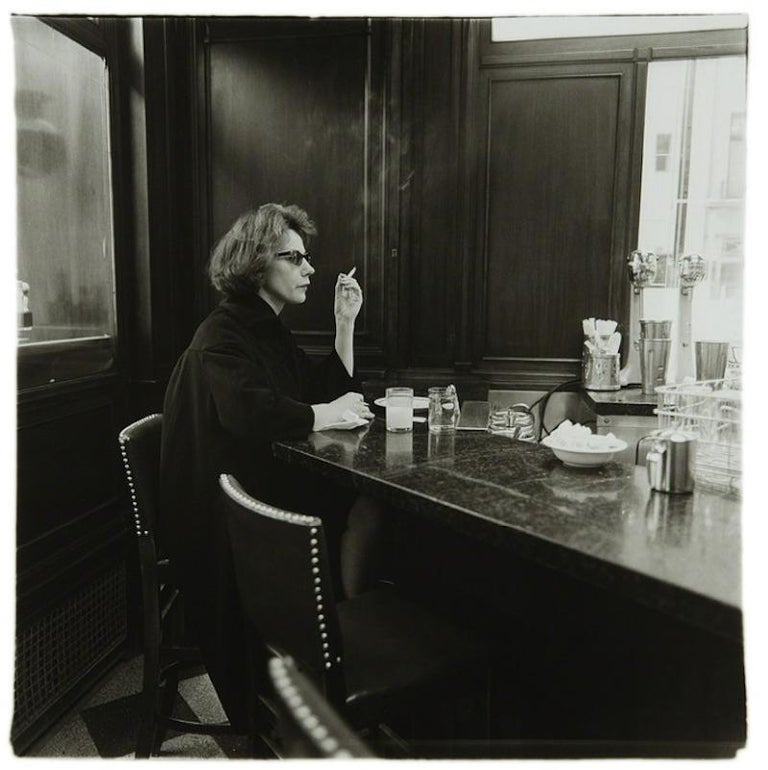Diane Arbus Black and White Photograph - Woman at a counter smoking, N.Y.C. 1962
