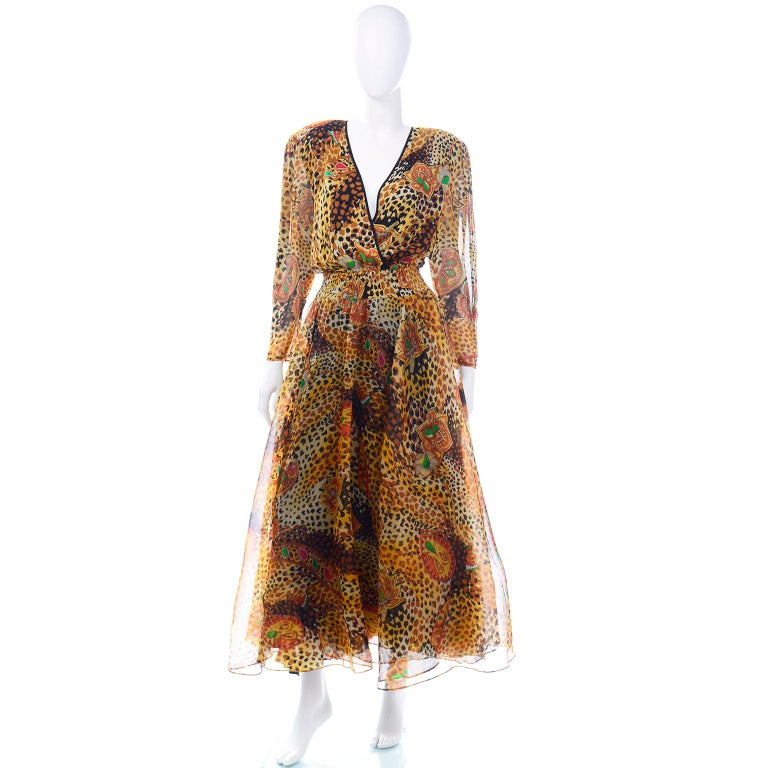 This beautiful vintage Diane Freis dress is made in a brown and black silk animal (cheetah or leopard) print with abstract jewels and leaves in shades of green, red, orange and yellow.  This stunning dress has a low v neckline, full circle skirt and