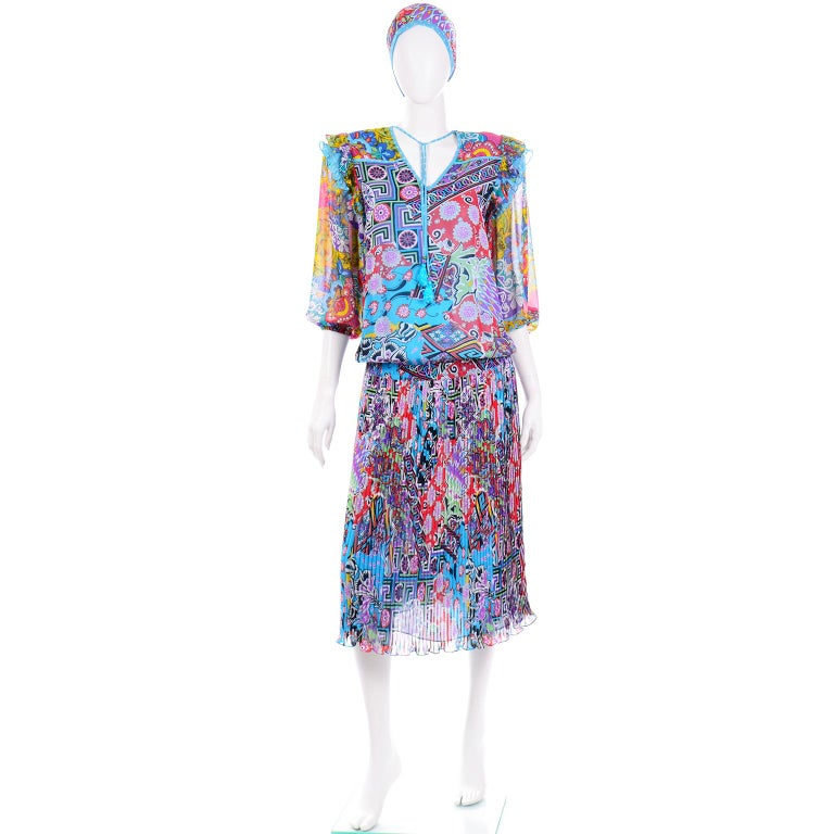 This is a fantastic Diane Freis blue abstract print dress with matching belt. The vibrant print is in lovely shades of blue, teal, turquoise, purple, pink, red, green, lime, yellow, white, and black. There are various patterns throughout the dress