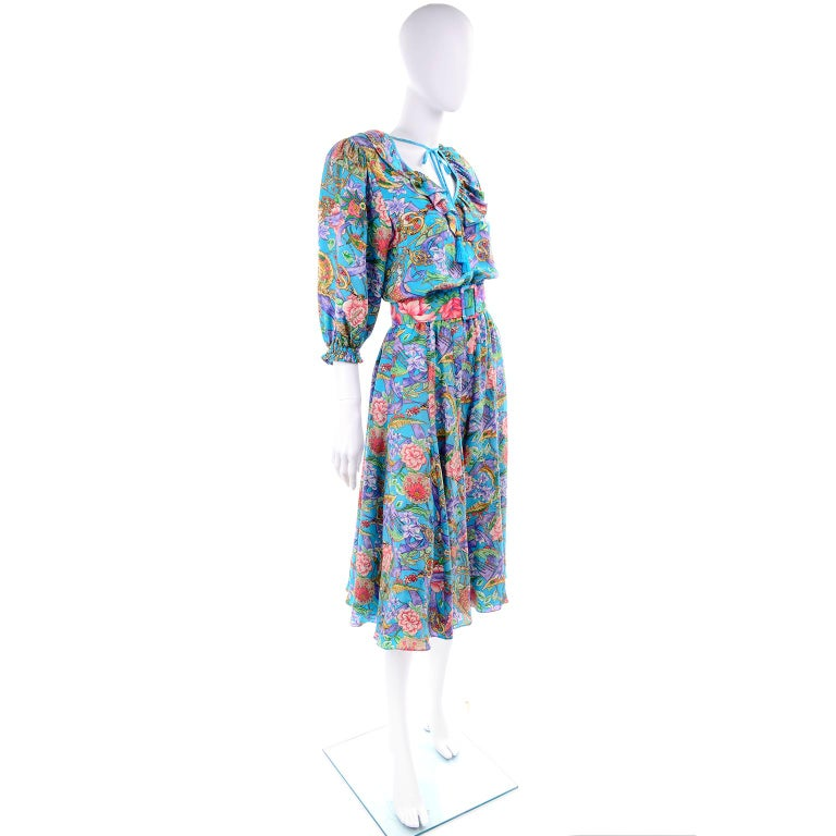 This is a really pretty 1980's vintage dress from Diane Freis from a woman who had a huge collection of Diane Freis dresses. The 100% silk fabric is in a turquoise blue, pink, gold and green floral print and the dress has its original fabric covered