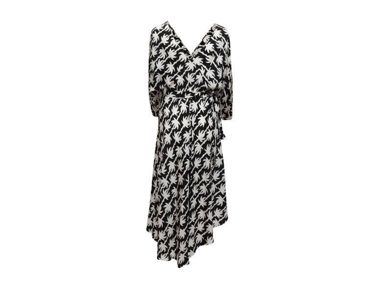 Product details: Black and white silk long sleeve wrap dress by Diane Von Furstenberg. Abstract print throughout. Surplice neckline. Asymmetrical hem. Tie closure at waist. 41
