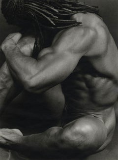 Edwin (a muscular nude male with dreadlocks flowing rests his head on a knee)