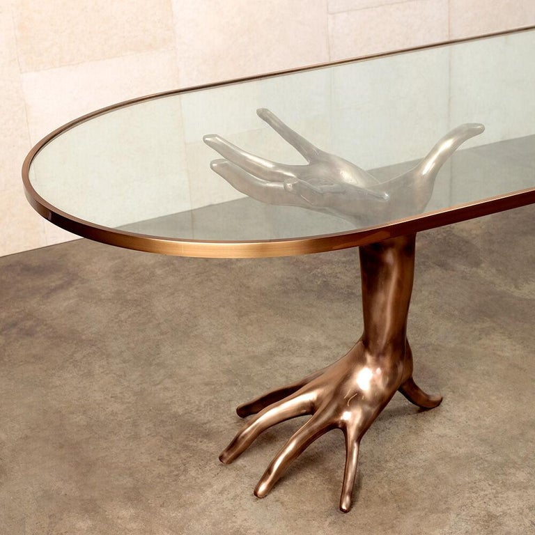 The luxurious and sculptural Dichotomy Racetrack table is a stunning and unique statement table inspired by classical figurative decor. The two bases are cast in bronze and meticulously polished by hand. The tempered glass racetrack-shaped top is